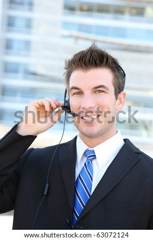 A young handsome customer service man with headset outside company building - stock photo