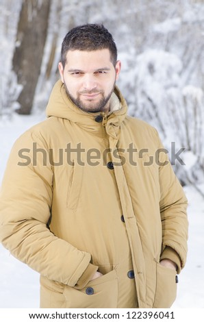 A young handsome guy in the forest during winter