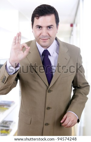A young handsome happy business man gesturing success at office building - stock photo