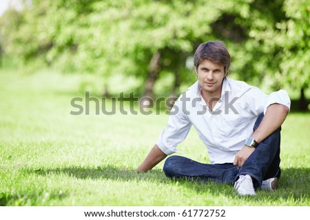 A young handsome man sits on the lawn - stock photo