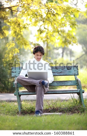 A young handsome man using laptop sitting on a bench in a park. looking and smiling into camera./man using laptop sitting on a green bench.  - stock photo