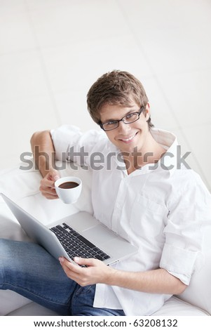 A young handsome man with a coffee and a laptop - stock photo