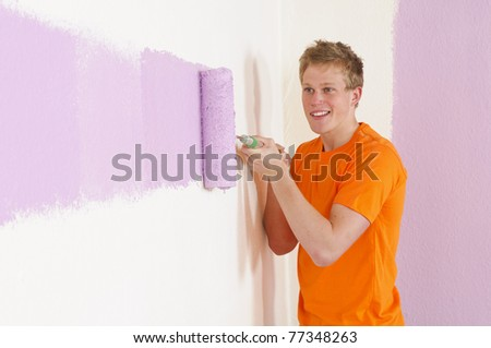 A young handsome man with blond hair in a orange T-shirt renovated his apartment. He strikes the wall with paint and a paint roller.