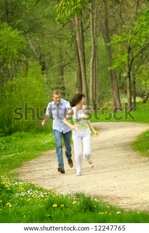 a young happy and smiling couple is playing tag