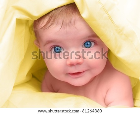 A young happy baby is looking into the camera and has bright blue eyes. The child is on a yellow blanket. Use it for a childhood, parenting or innocence theme. - stock photo