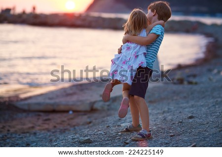A young happy boy and his little cute sister walking on the sea shore on a warm summer evening. Friendship between siblings.