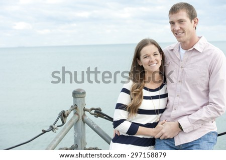 A young happy caucasian couple on a sunny day with the clouds in the background at the pier. - stock photo
