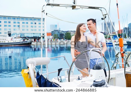 A young happy Caucasian couple sailing together on a boat in the ocean. - stock photo