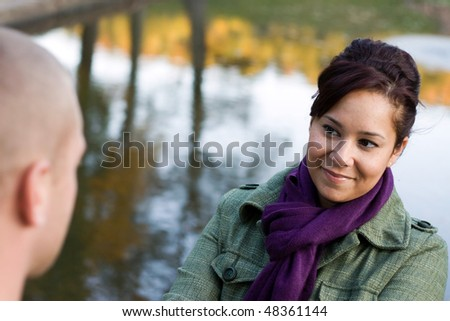 A young happy couple enjoying each others company outdoors in the fall. - stock photo