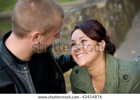 A young happy couple looking fondly at one another outdoors.  Shallow depth of filed with focus in the woman. - stock photo