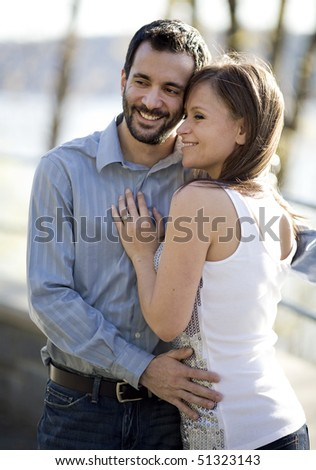 A young, happy couple posing on a sunny day. - stock photo