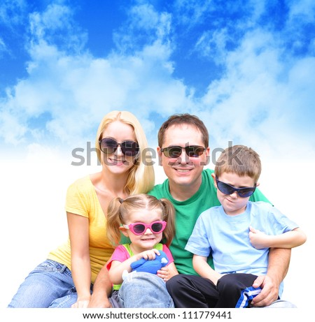 A young happy family is wearing sunglasses and colorful clothing against a nature sky background. There is a text area for a message. Use it for a vacation or weather concept.