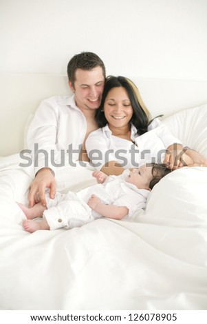 A young happy family with their 4  month old son.... - stock photo
