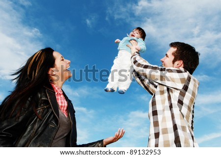 A young happy family with their 4  month old son - stock photo