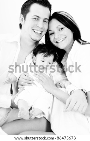 A young happy family with their 4  month old son sitting in bed
