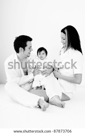 A young happy family with their 4  month old son sitting in bed - stock photo