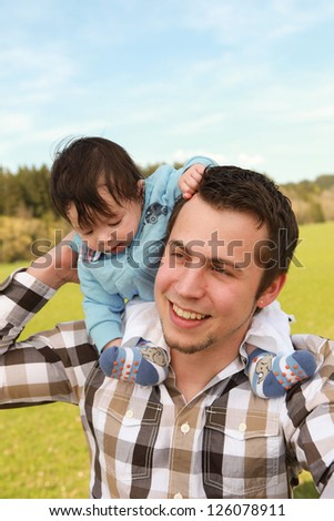 A young happy father 25 years with his 4  month old son.