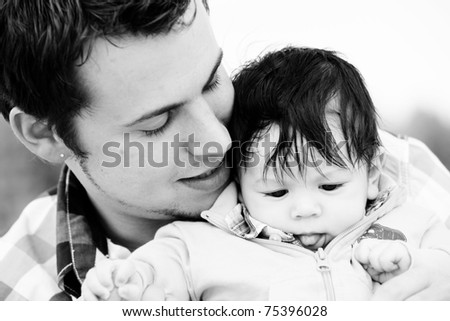 A young happy father 25 years with his 4  month old son.... - stock photo