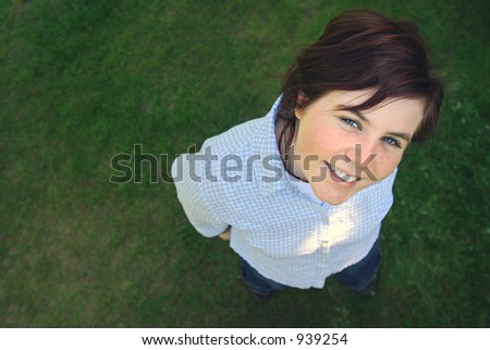 a young happy girl looking up at the camera. space for copy. - stock photo
