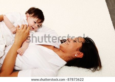 A young happy mother 22 years with her 4  month old son.... - stock photo