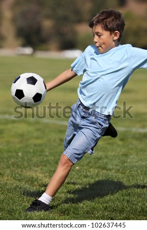 A young happy school age boy prepares to kick a soccer ball in a field on a sunny day - stock photo