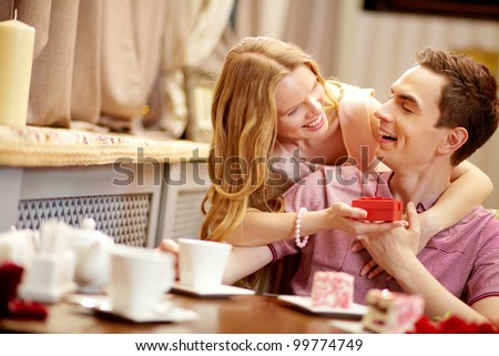 A young happy woman showing giftbox to her boyfriend - stock photo