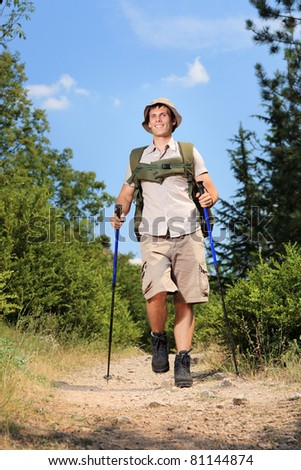A young hiker with trekking poles hiking in the mountain - stock photo