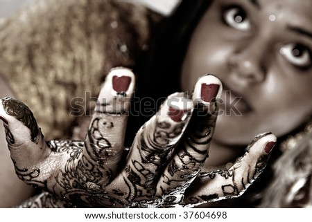 A young Hindu Bride shows off her traditional Henna designs before the wedding - stock photo