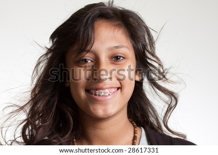 A young hispanic girl wearing braces.  Smiling at the camera. White background - stock photo