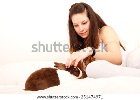 A young hispanic girl with a rabbit in the bed.   - stock photo