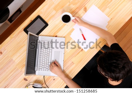 A young hispanic man working on a wooden desk with a laptop. - stock photo