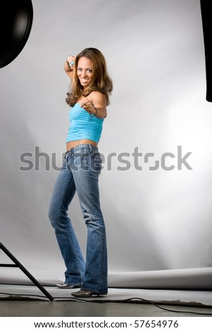 A young hispanic woman posing in a studio setting. A behind the scenes look at the setup using multiple lights with soft boxes and a beauty dish. - stock photo