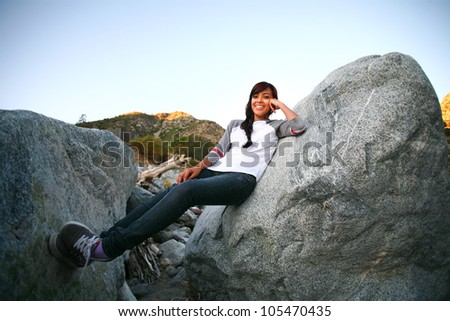 A young Hispanic woman relaxes between large boulders in an outdoor setting around sunset. - stock photo