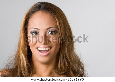 A young hispanic woman with a big smile on her face isolated over silver. - stock photo