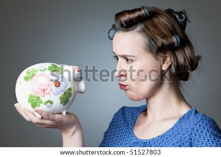 A young housewife taking a skeptical look at household finances. - stock photo
