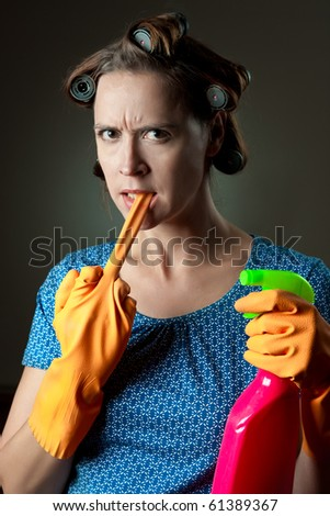 A young housewife with a rubber glove in a cleaning scenario, unhappy. - stock photo