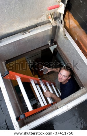 A young HVAC technician climbing up a ladder to the rooftop. - stock photo