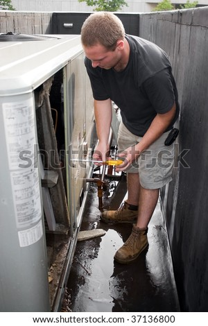 A young HVAC technician working on a commercial air system on the rooftop. - stock photo