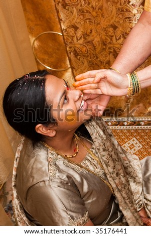 A young indian bride takes part in a pre-wedding ceremony - stock photo