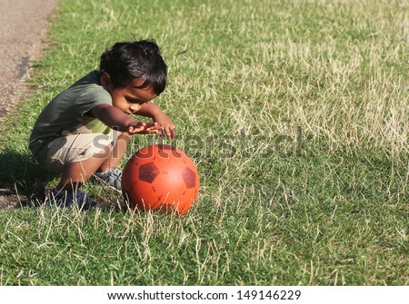 A Young Indian Toddler playing with a red ball in a green grass of a garden or a park - stock photo