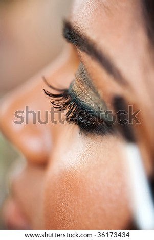 A young Indian woman has eye make-up applied at a salon - stock photo