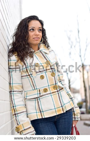 A young Indian woman posing outdoors in an urban setting. - stock photo