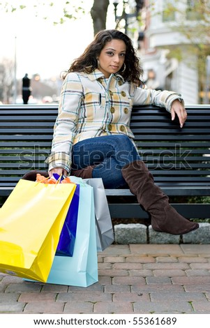 A young Indian woman taking a break on a park bench while out shopping in the city. - stock photo