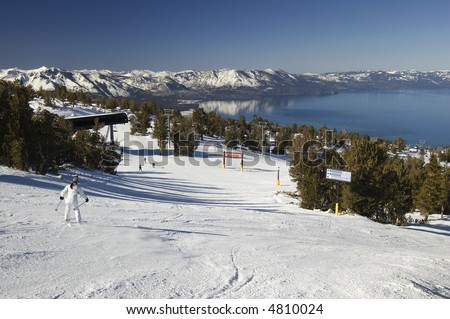 A young inexperienced female skier going down the slope on a lake tahoe ski resort. - stock photo
