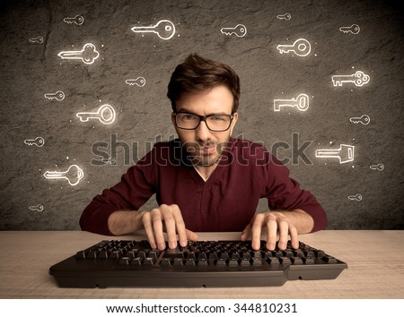 A young internet geek working online, hacking login passwords of social media users concept with glowing drawn keys on the wall - stock photo