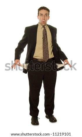 A young isolated businessman holding out his pockets to show he has no money - stock photo