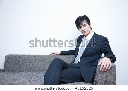 A young Japanese businessman wearing suit is sitting on the sofa