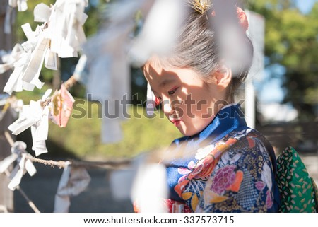 A young Japanese girl in a kimono outdoors at a shrine tying her fortune paper on a rope.