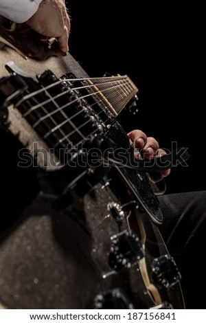 a young jazzer with a black acoustig guitar over black background - stock photo