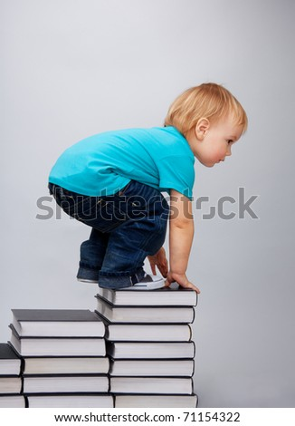 A young kid has climbed on top of the books steps - stock photo